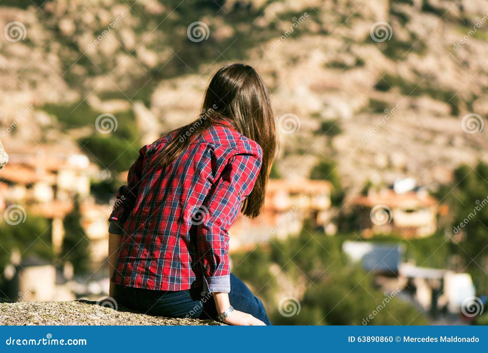 Giovane donna che si siede nel pozzo delle montagne, fissante nello PS