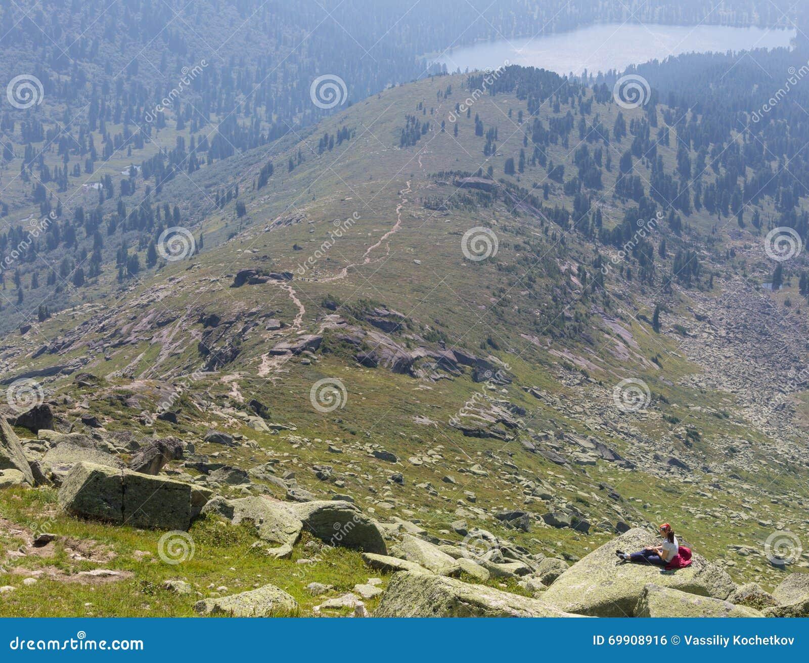 Giovane donna che si siede su una roccia con lo zaino e che guarda all orizzonte