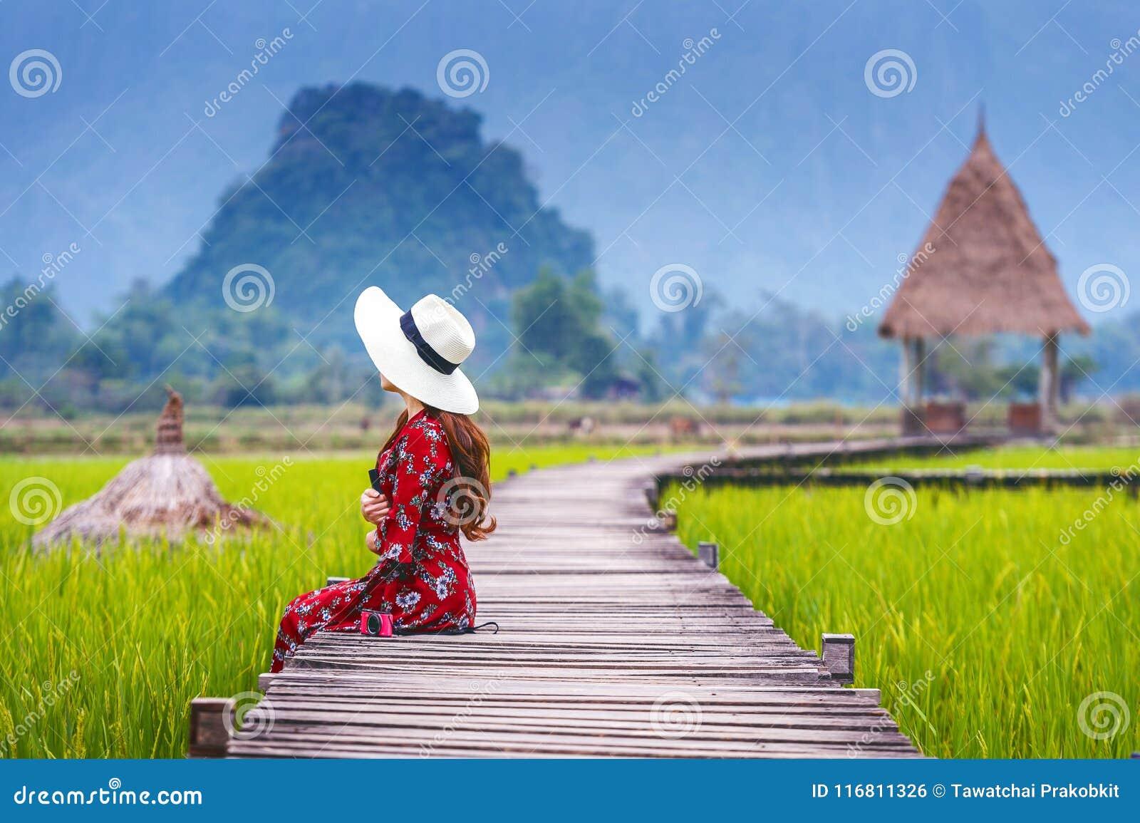 Giovane donna che si siede sul percorso di legno con il giacimento verde del riso in Vang Vieng, Laos