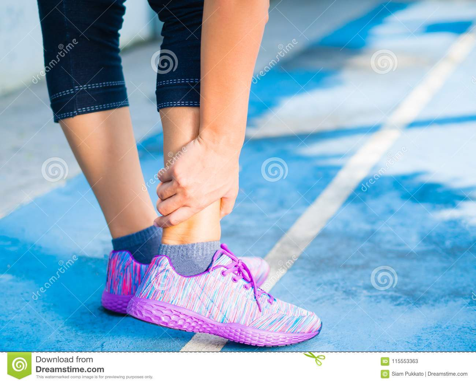 Giovane donna che soffre da una ferita alla caviglia mentre esercitandosi e correndo