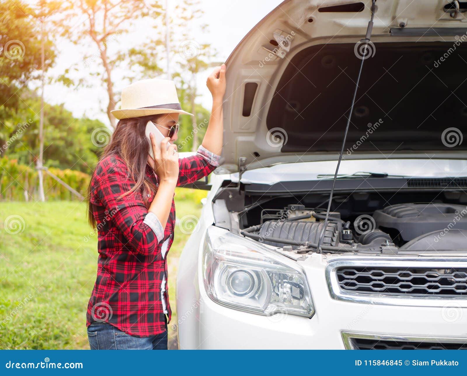 Giovane donna che sta dal lato della strada con l automobile rotta