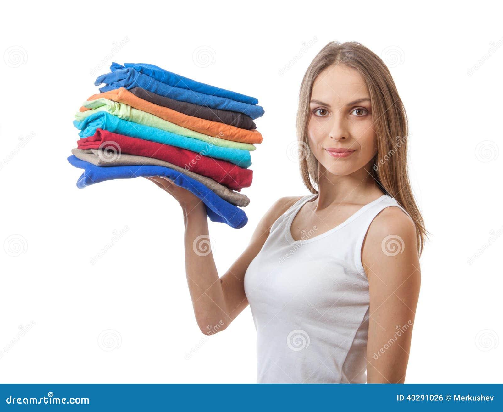 Giovane donna che tiene un mucchio dei vestiti