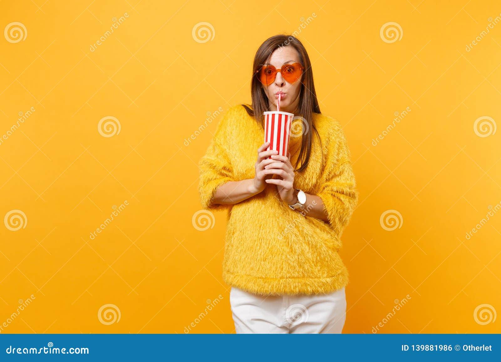 Giovane donna colpita in maglione della pelliccia e vetri arancio del cuore che beve cola o soda dalla tazza di plastica isolata