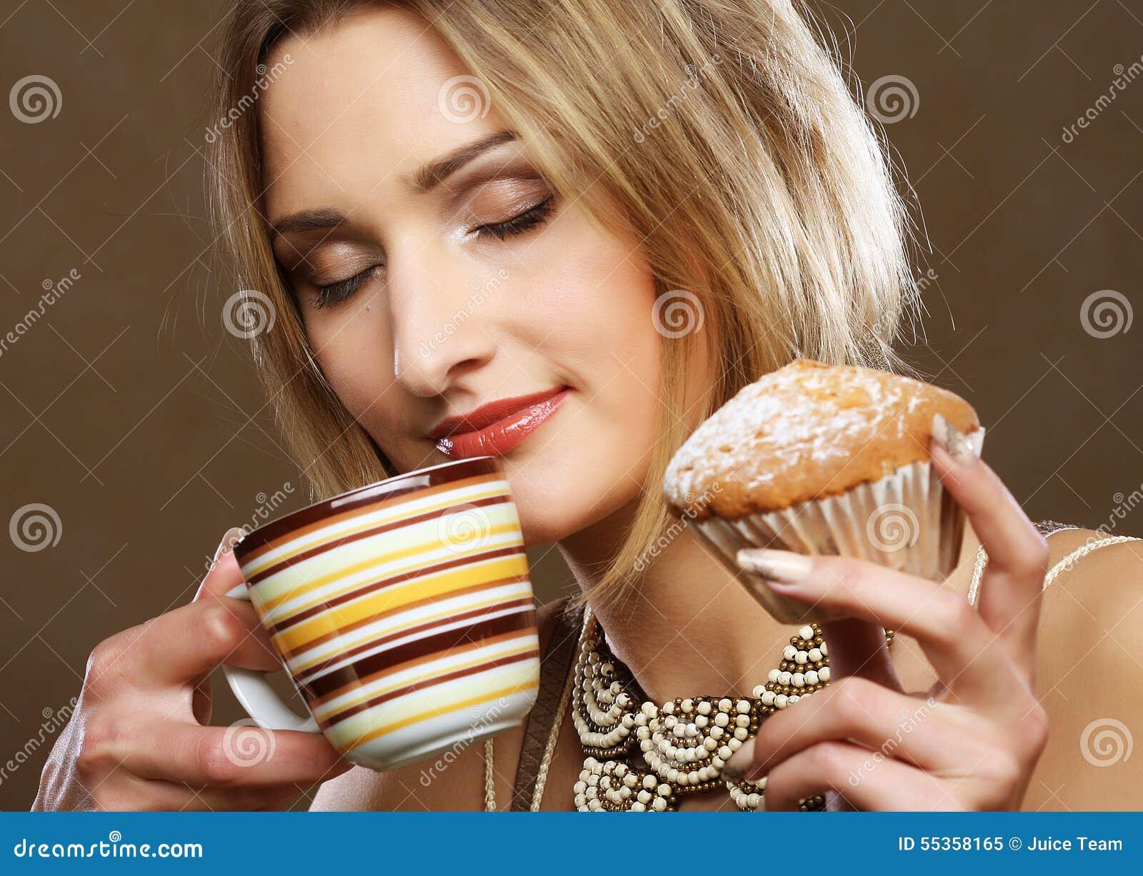 Giovane donna con caffè ed i biscotti