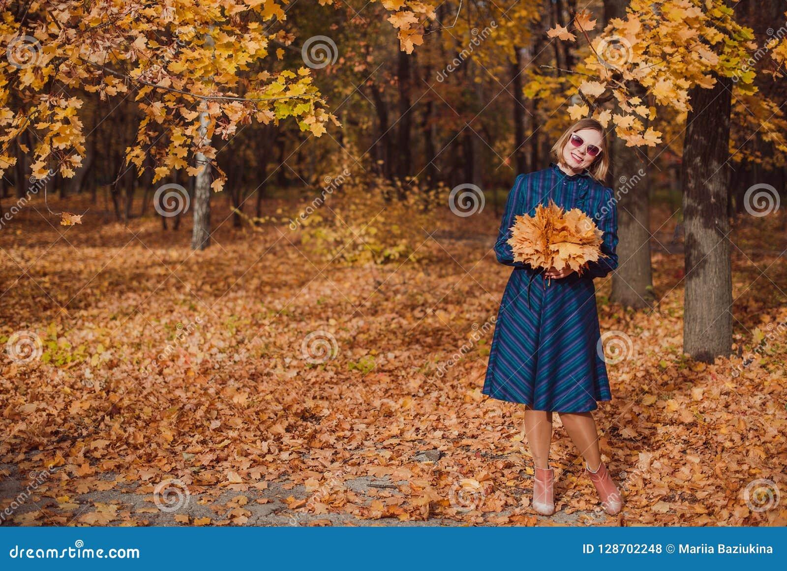 Giovane donna con capelli biondi che portano vestito blu che cammina nel parco di autunno