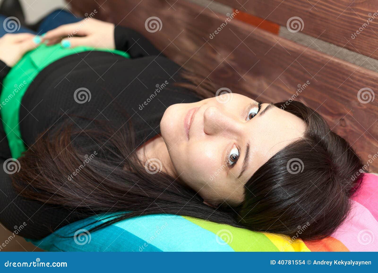 Giovane donna con distendere e gli sguardi lunghi dei capelli alla macchina fotografica