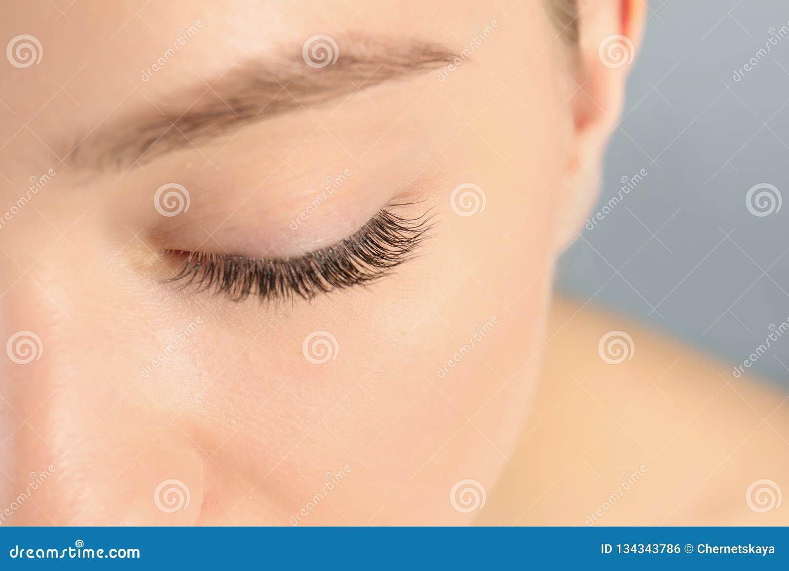 Giovane donna con i bei cigli lunghi su fondo grigio, primo piano