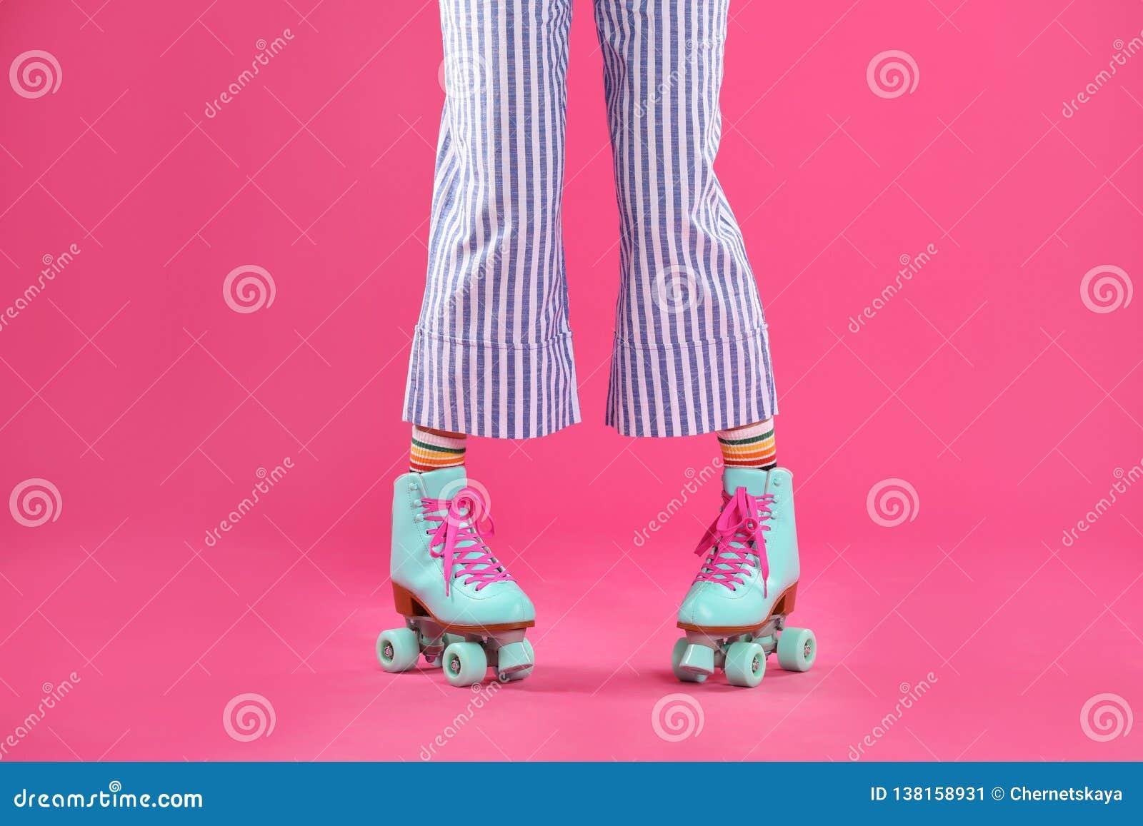 Giovane donna con i retro pattini di rullo sul fondo di colore