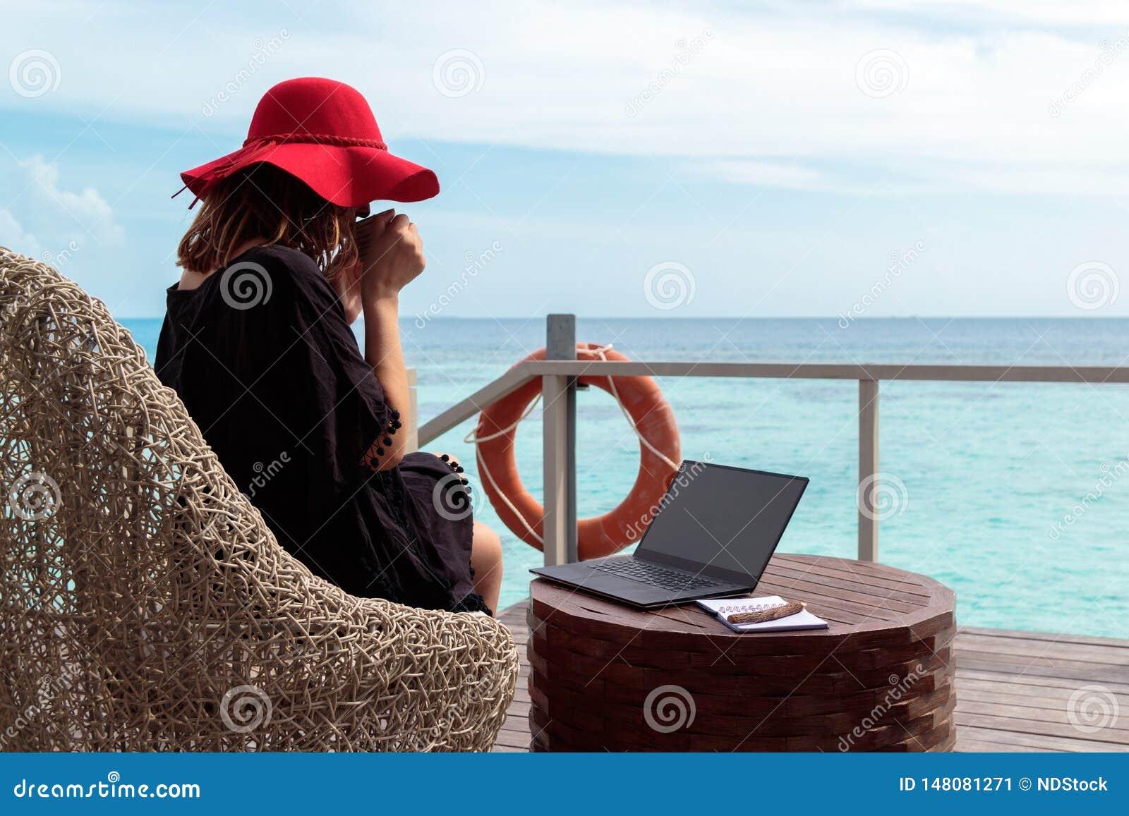 Giovane donna con il caffè bevente del cappello rosso e lavorare ad un computer in una destinazione tropicale