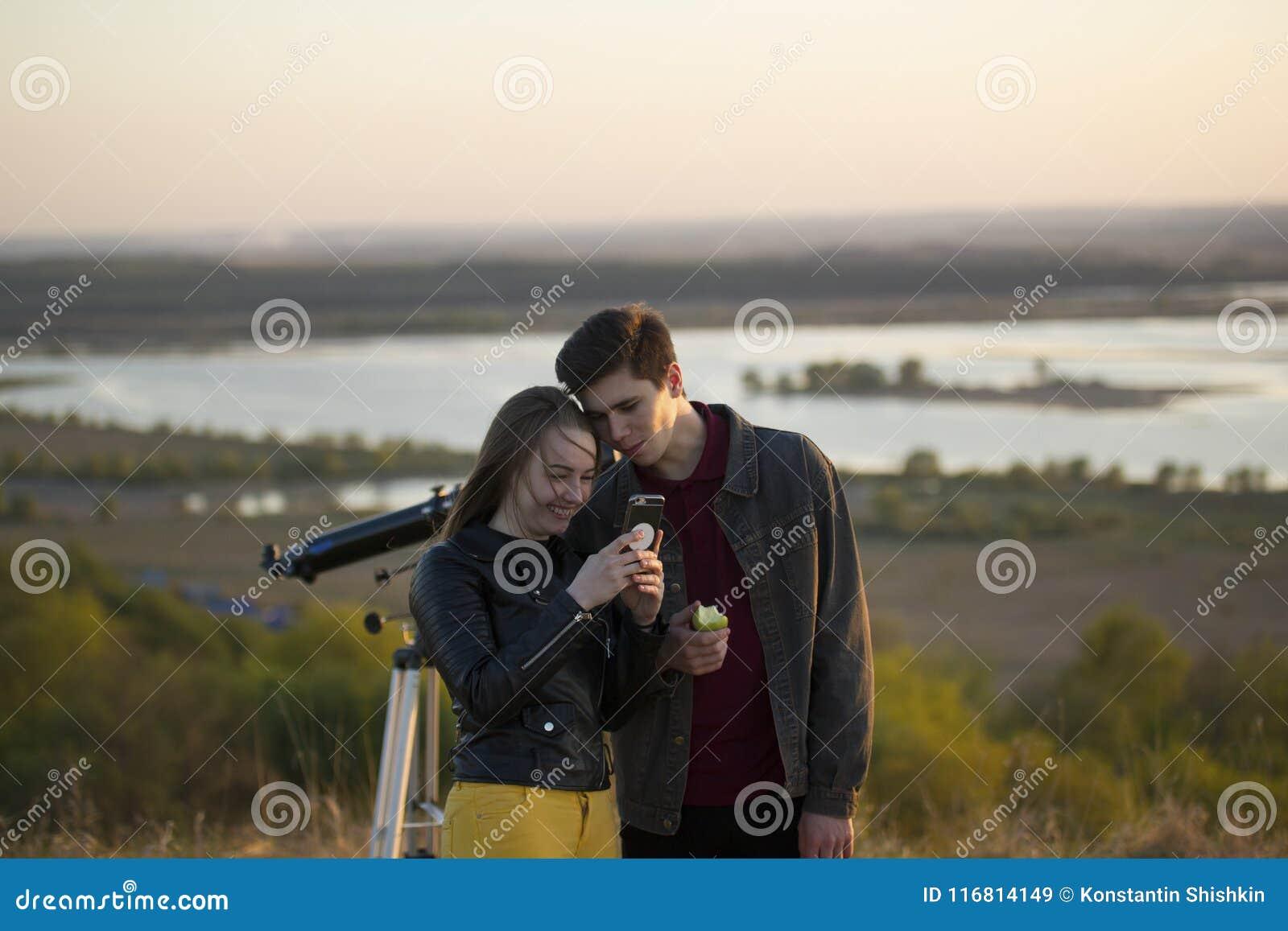 Giovane donna con il ragazzo che considera il telefono al tramonto di estate