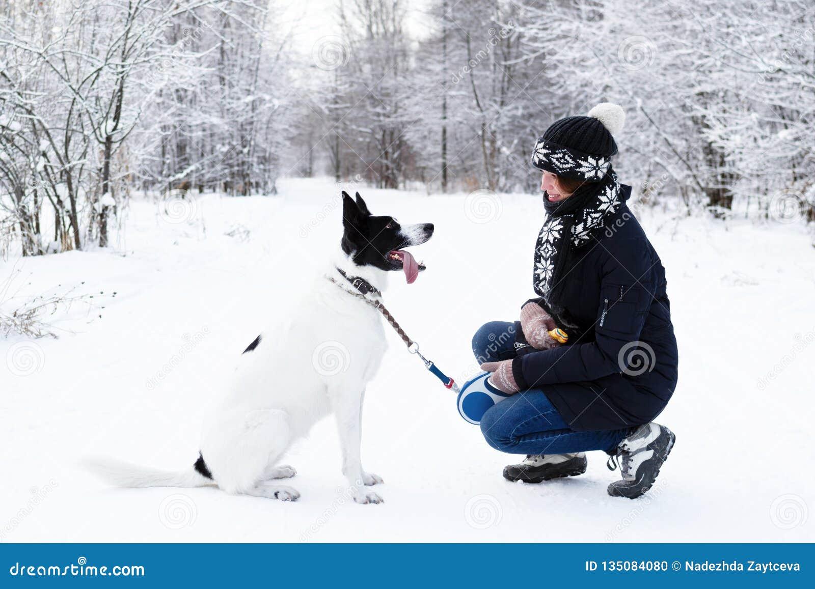 Giovane donna con il suo cane in bianco e nero su una passeggiata nella foresta di inverno