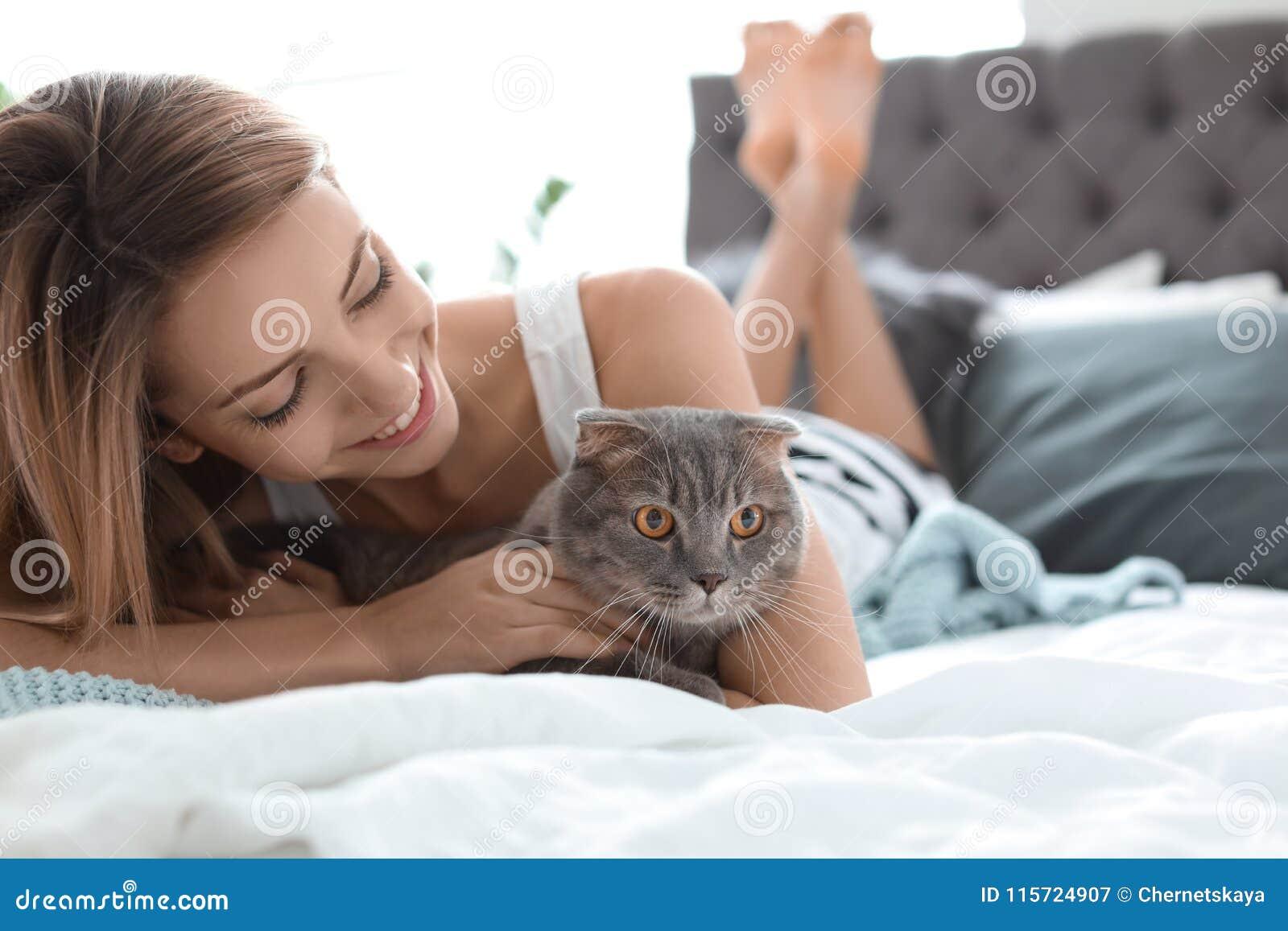 Giovane donna con il suo gatto sveglio dell animale domestico sul letto