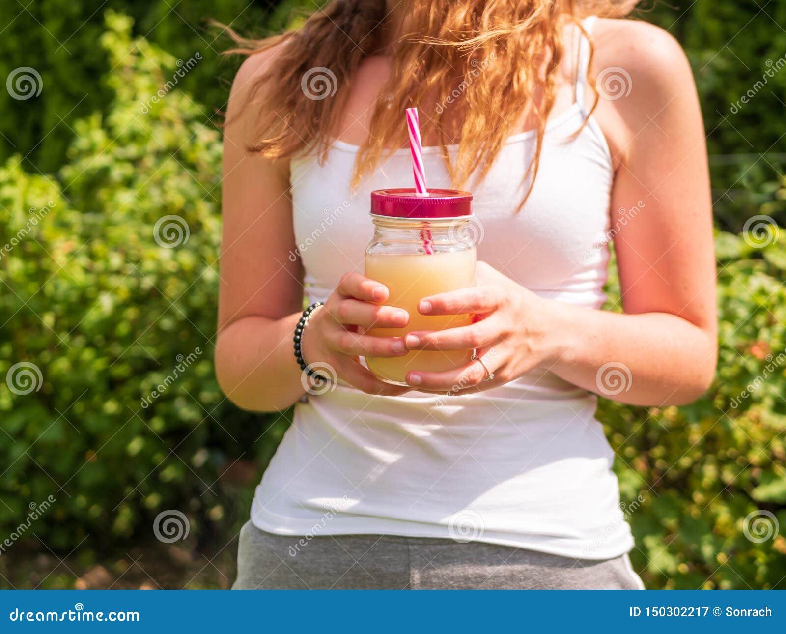 Giovane donna con la bevanda di estate in sue mani