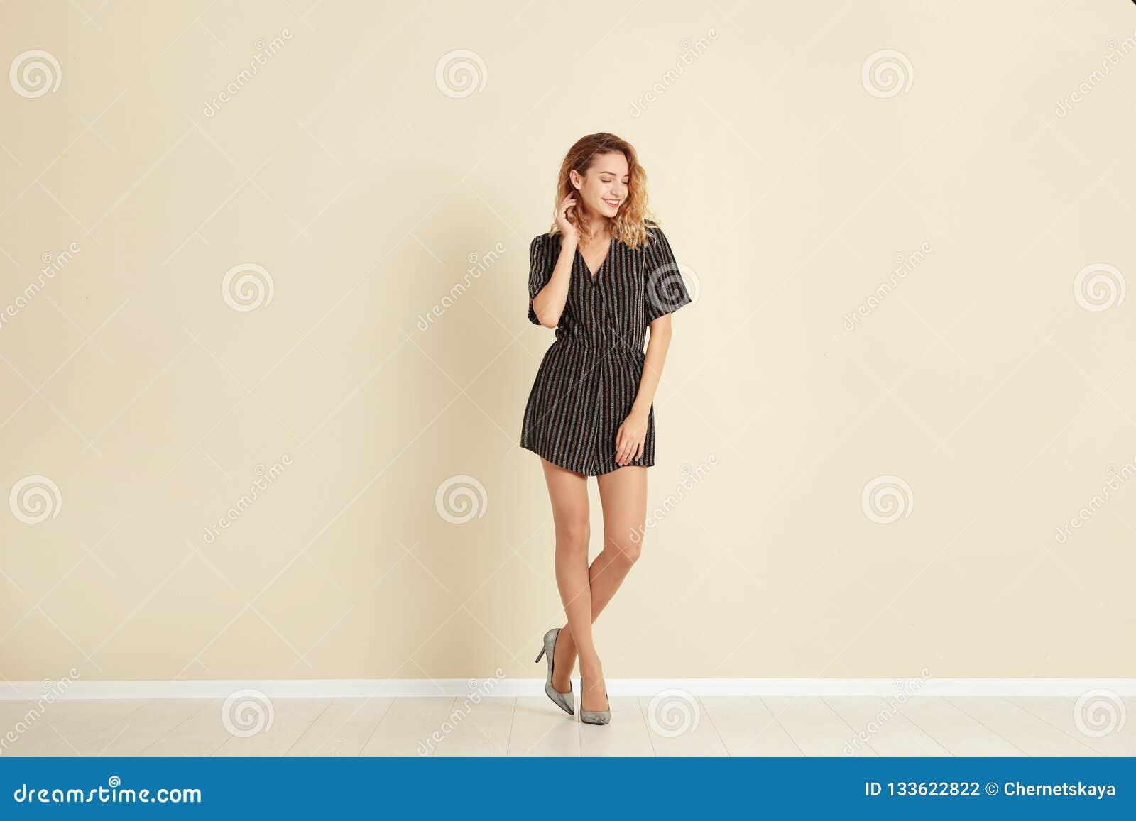 Giovane donna con le belle gambe lunghe in attrezzatura alla moda