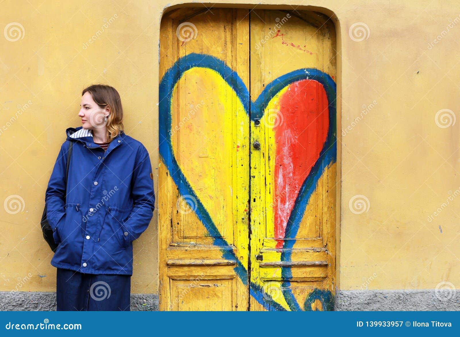 Giovane donna contro la parete gialla e porte di legno con i graffiti