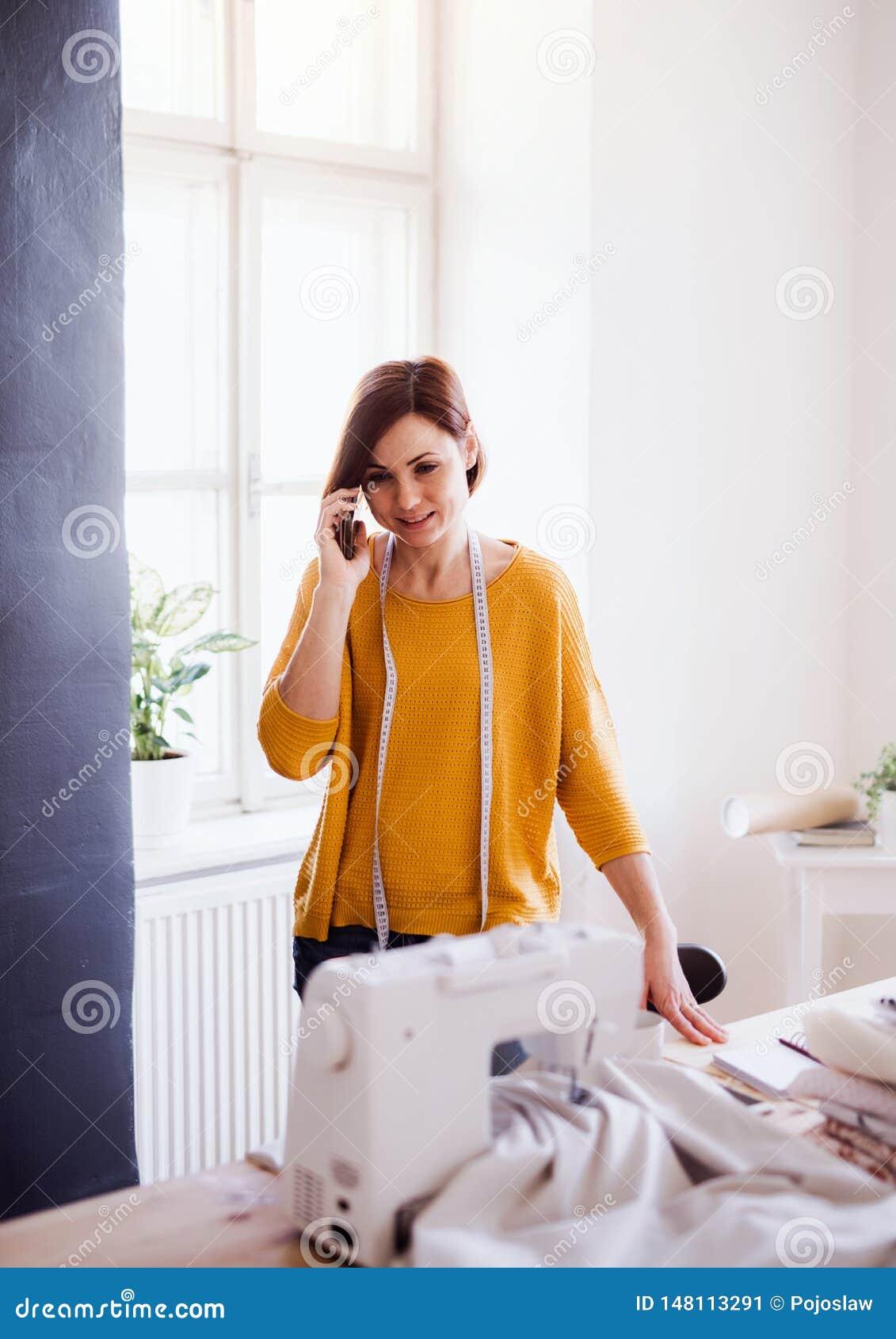 Giovane donna creativa in uno studio, facendo uso dello smartphone Una partenza di adattamento dell affare