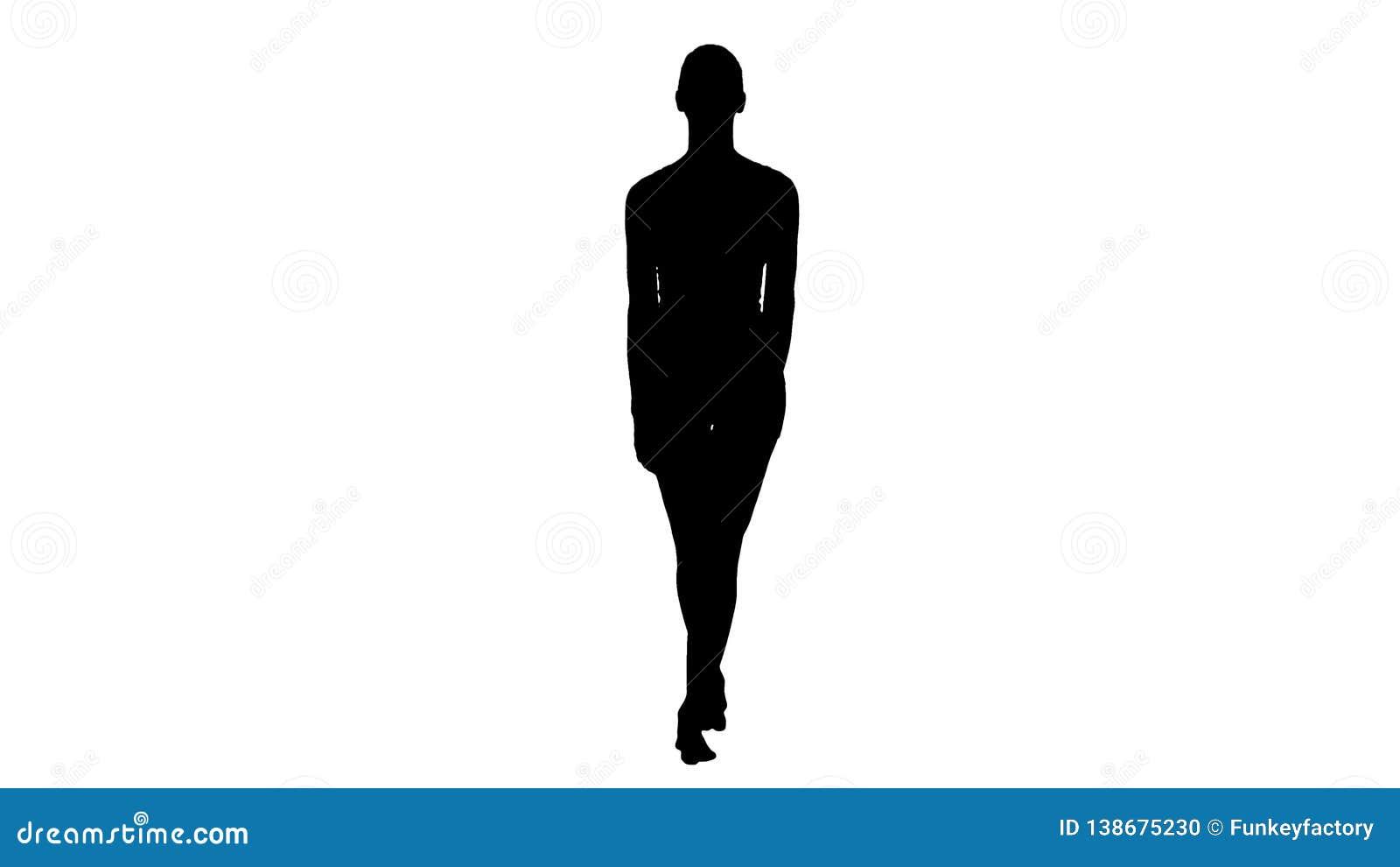 Giovane donna della siluetta che cammina a piedi nudi in vestiti bianchi di sport e che sorride ampiamente