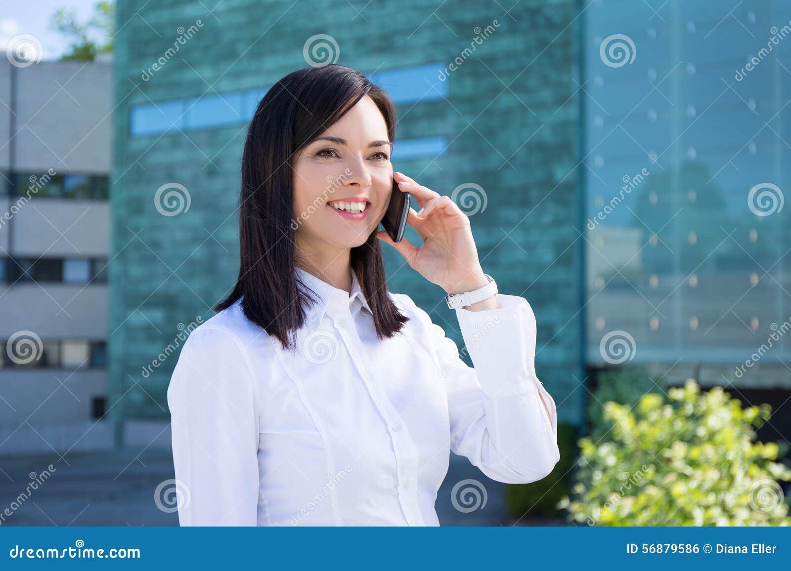 Giovane donna di affari che parla sullo smartphone alla via