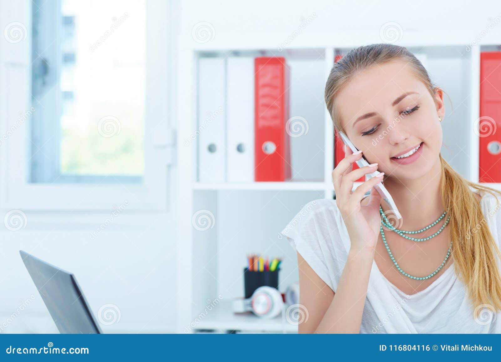 Giovane donna di affari sorridente che parla sul telefono e che scrive le note nell ufficio