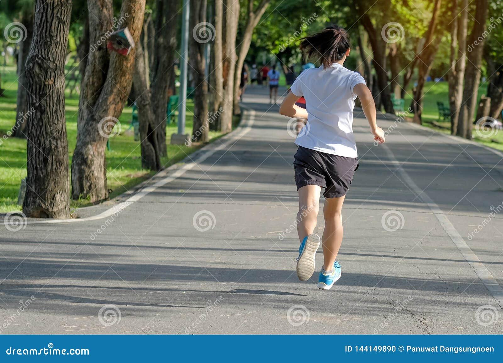 Giovane donna di forma fisica che corre nel parco all aperto, nel corridore femminile che camminano sulla strada fuori, pareggiar