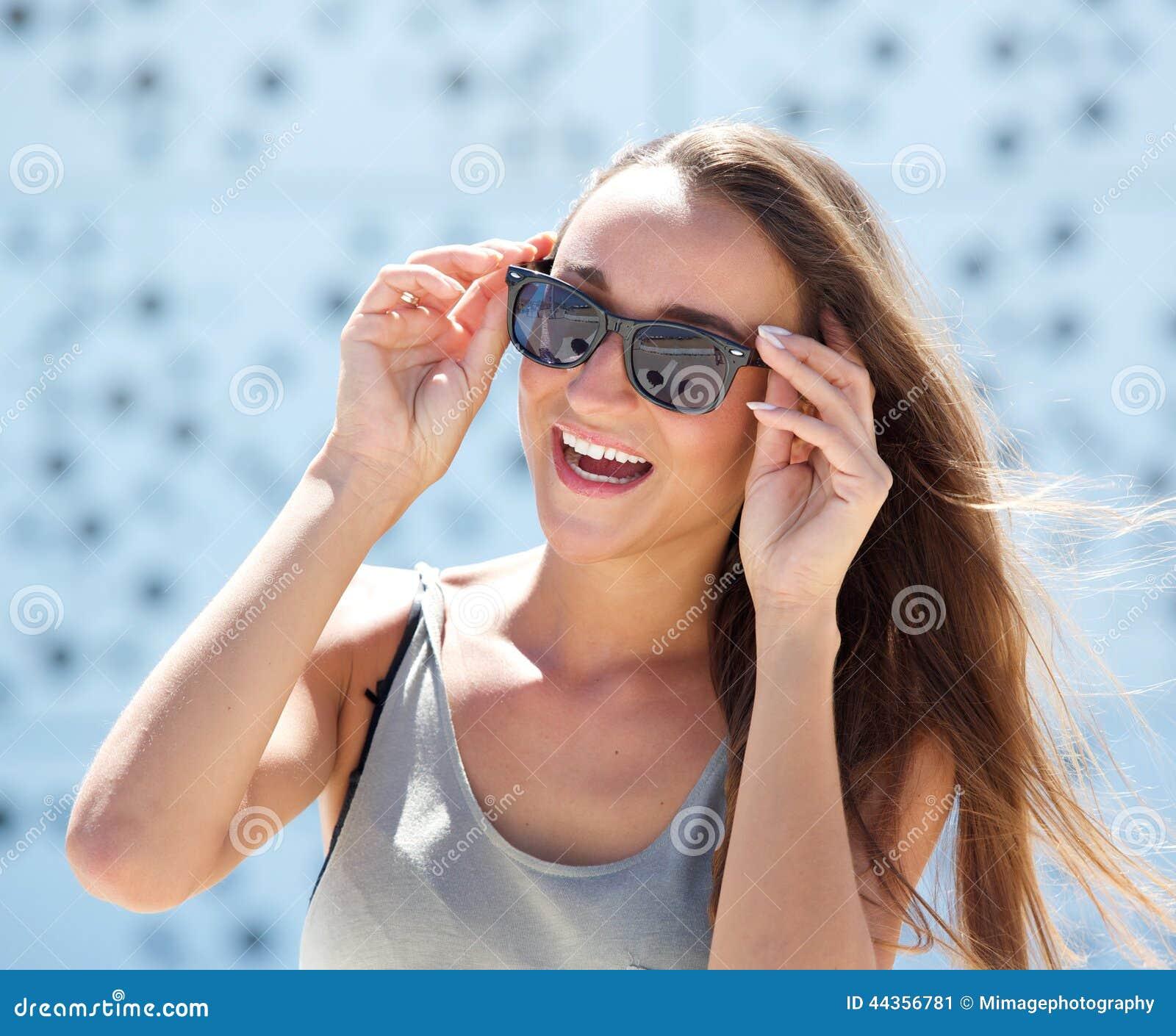 Giovane donna di risata con gli occhiali da sole