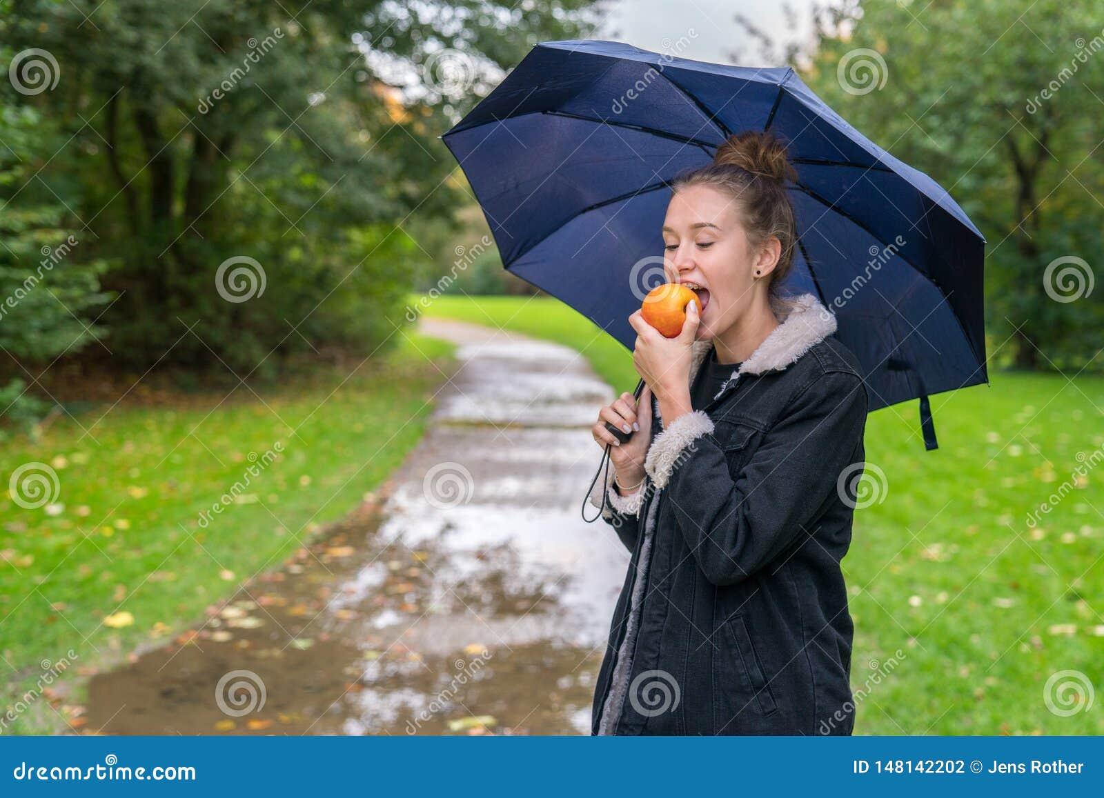 Giovane donna di Smilling che mangia mela all aperto