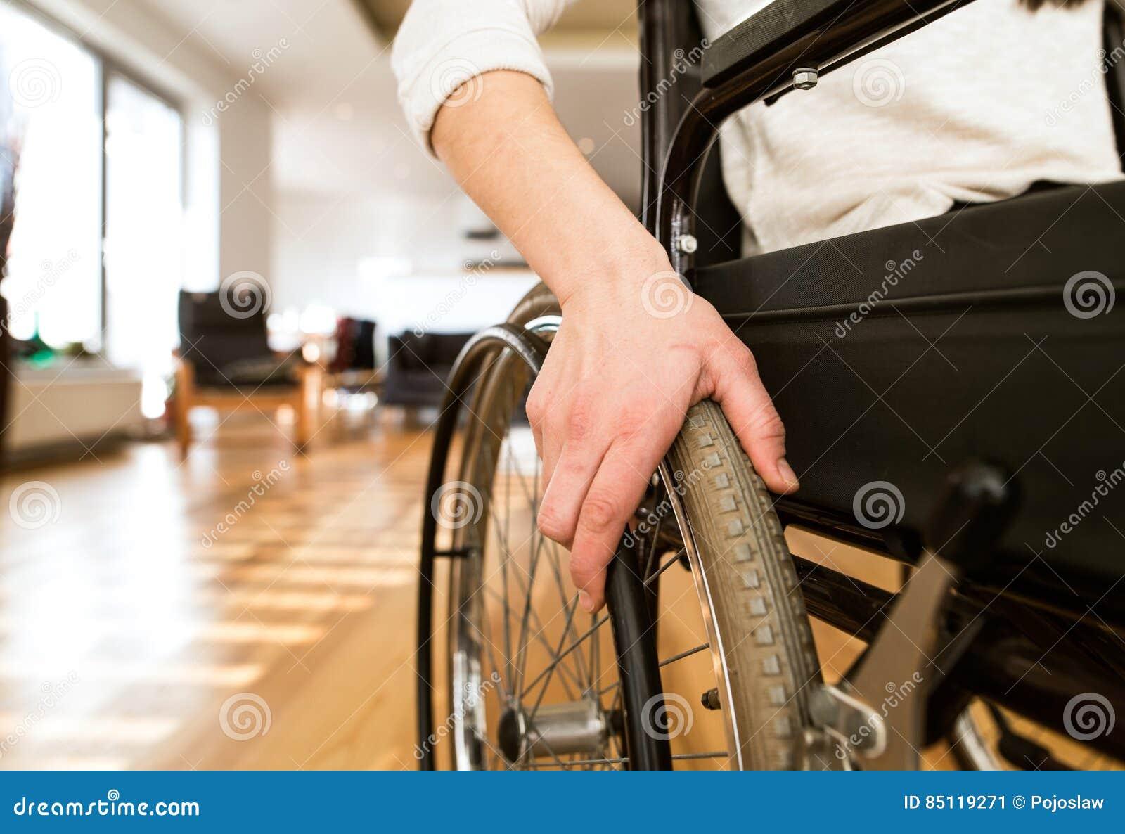 Giovane donna disabile in sedia a rotelle a casa in salone