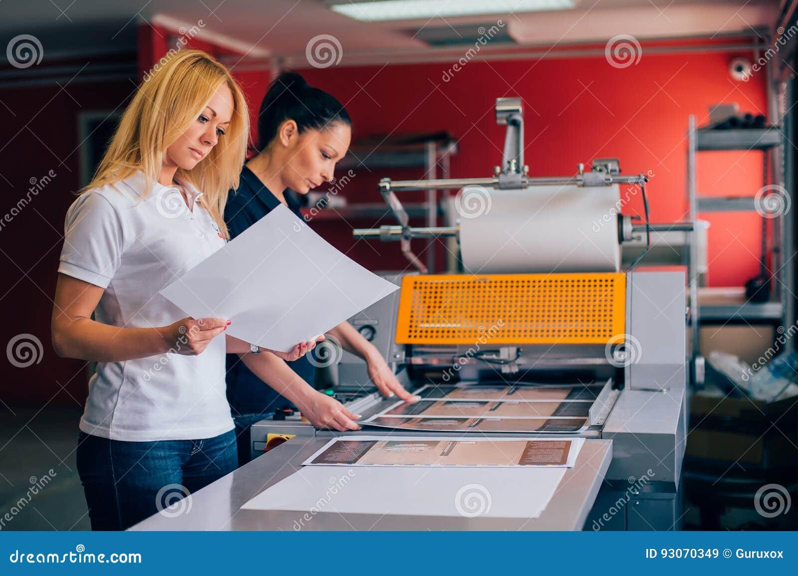 Giovane donna due che lavora nella fabbrica di stampa