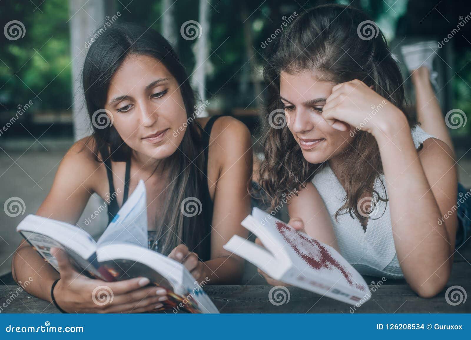 Giovane donna due che si trova nell oscillazione sulla spiaggia, libri di lettura