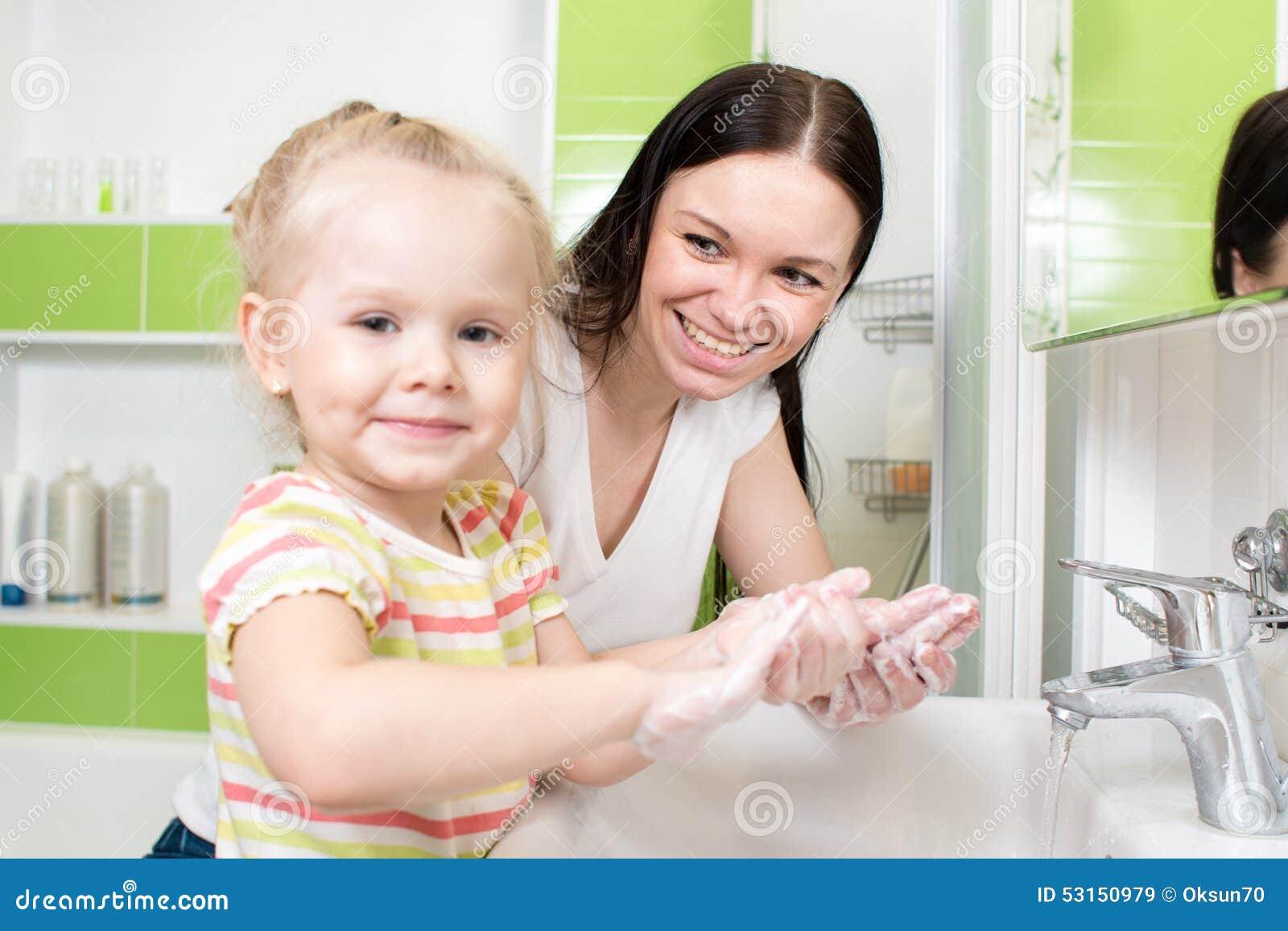 Giovane donna e le sue mani di lavaggio della figlia con