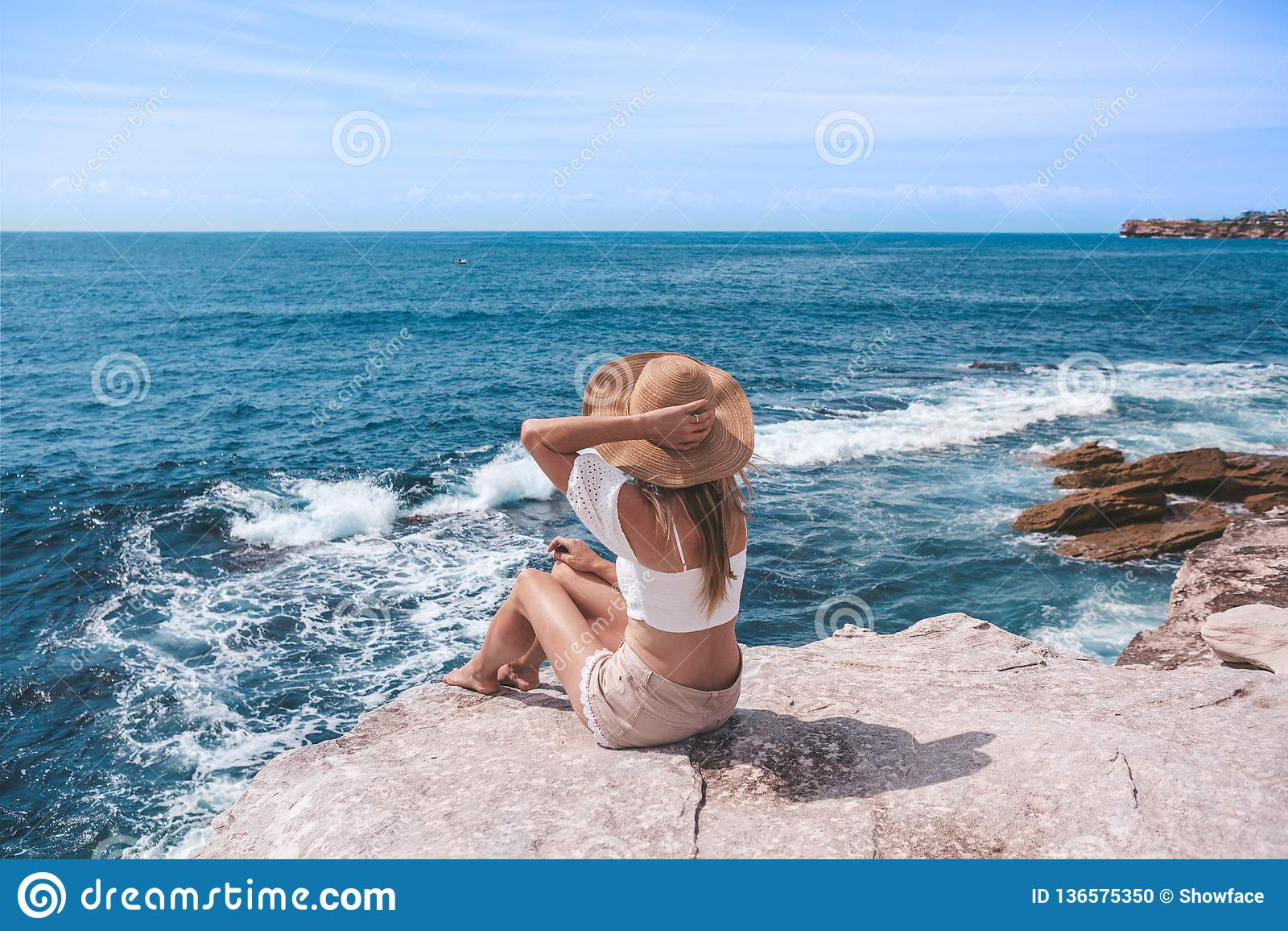 Giovane donna elegante che si siede dall oceano