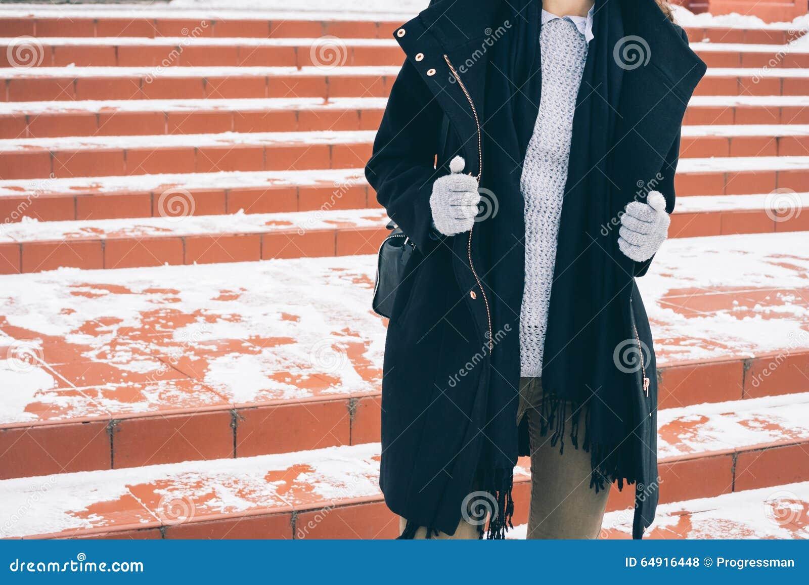 Giovane donna esile in cappotto nero sbottonato, in un maglione grigio ed in guanti