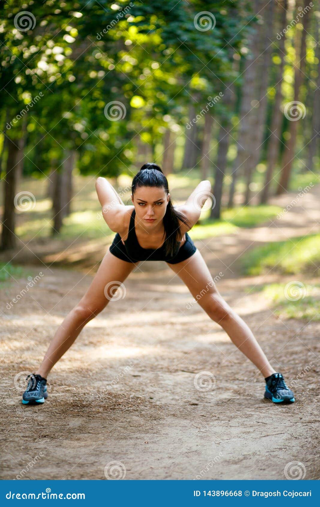Giovane donna esile castana nell allenamento degli abiti sportivi fuori, facendo allungando gli esercizi del corpo in parco