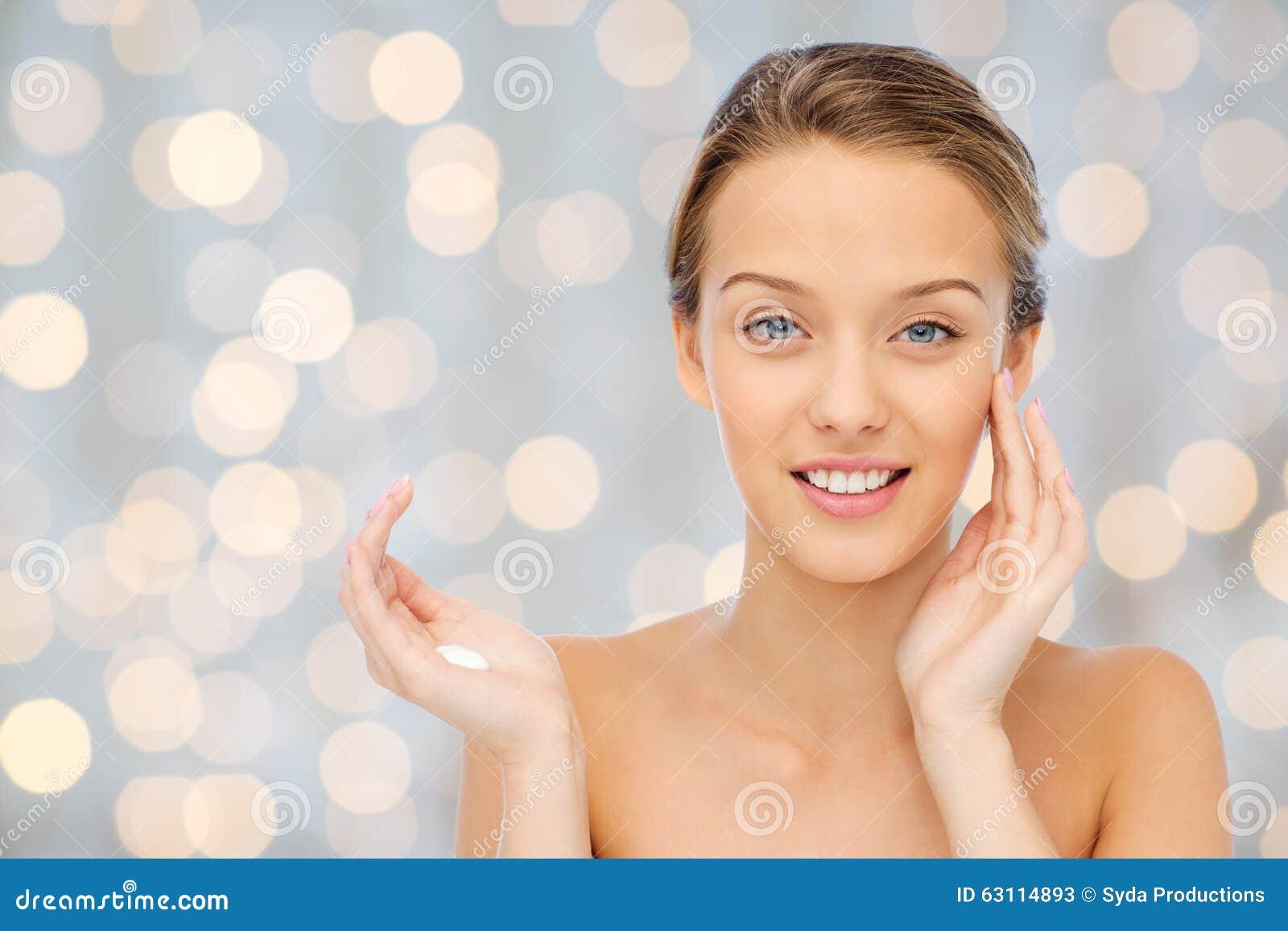 Giovane donna felice che applica crema al suo fronte for Suo e suo bagno