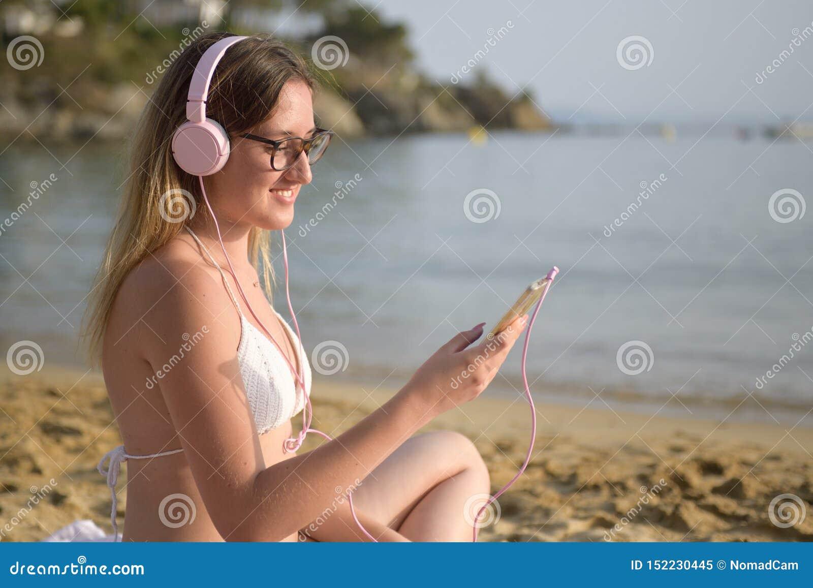 Giovane donna felice che ascolta la musica sulla spiaggia