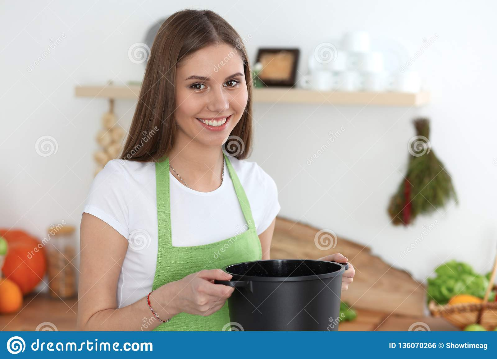 Giovane donna felice che cucina minestra nella cucina Pasto sano, stile di vita e concetto culinario Ragazza sorridente dell alli