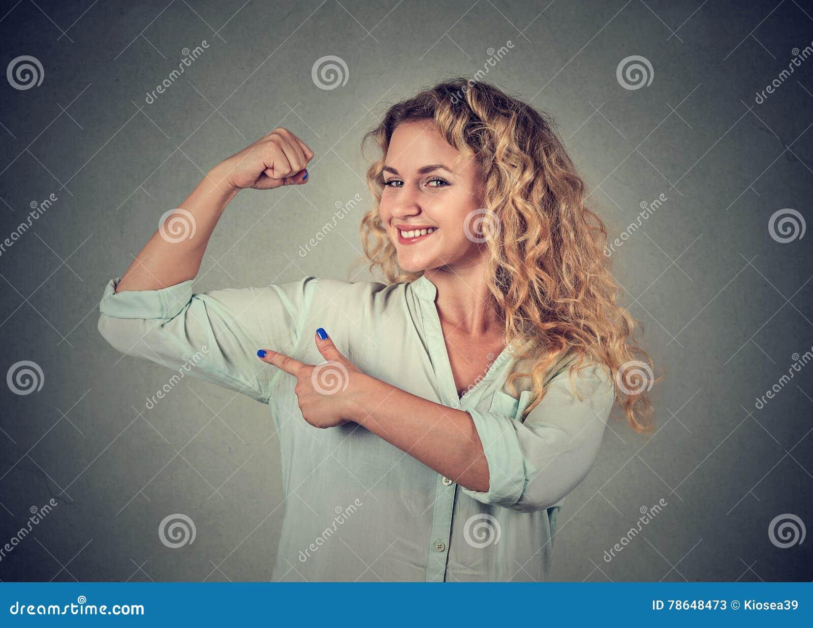Giovane donna felice che flette i muscoli gli che mostrano forza