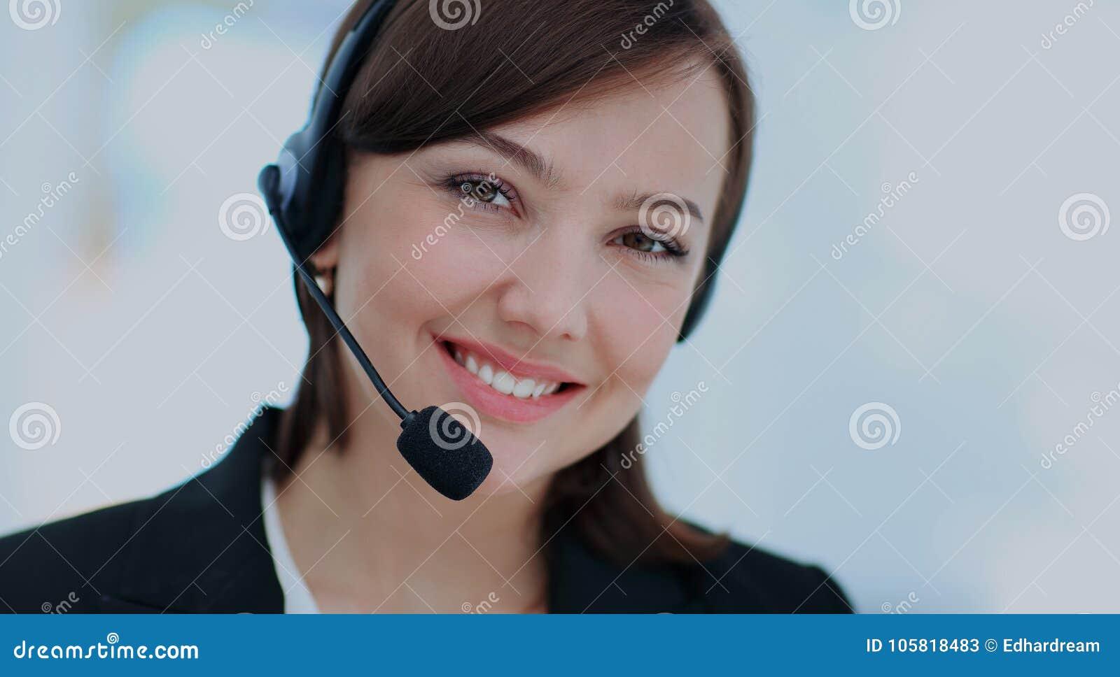 Giovane donna felice che lavora al callcenter, facendo uso della cuffia avricolare