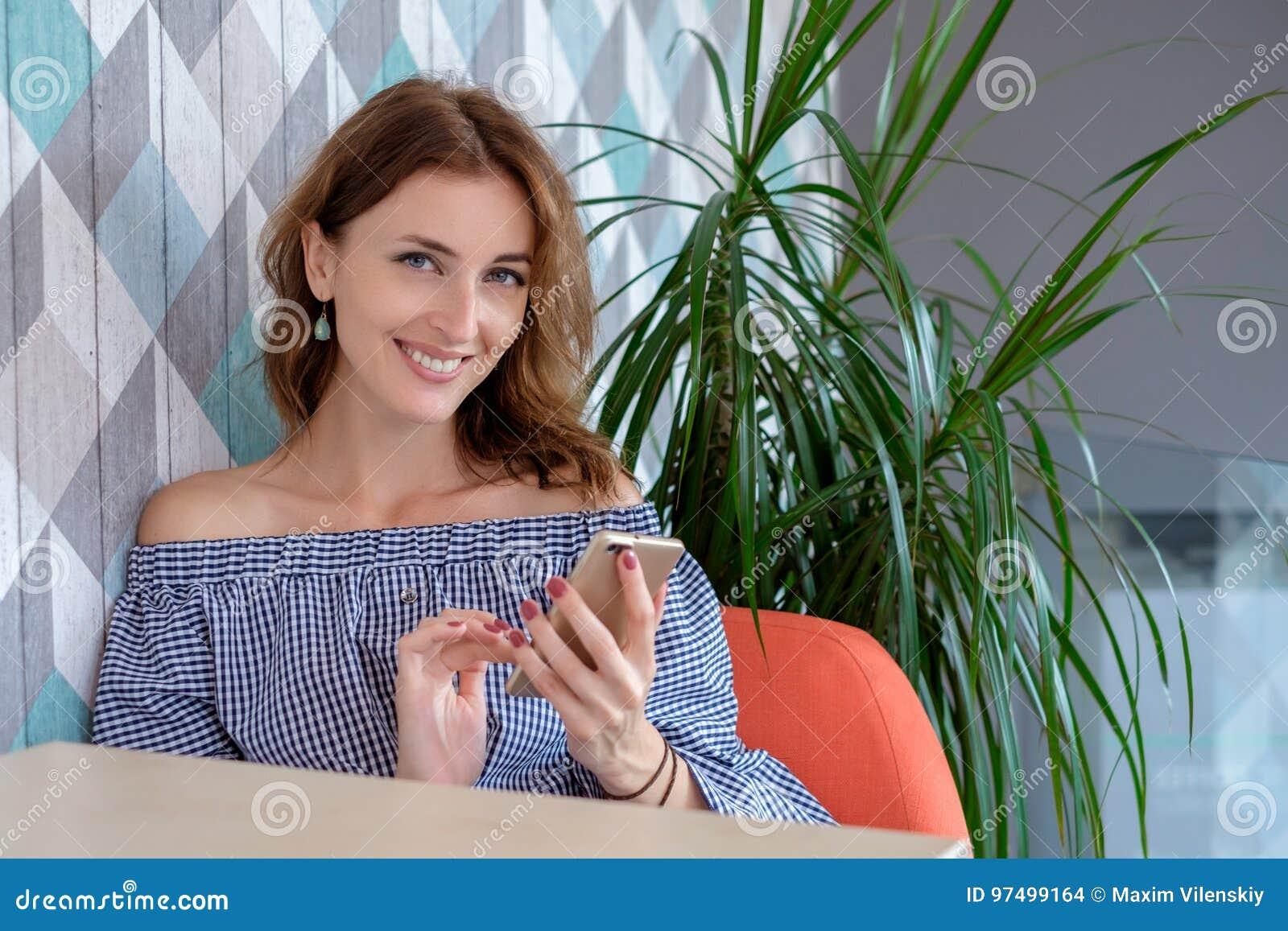 Giovane donna felice che parla sul telefono cellulare con l amico mentre sedendosi da solo nell interno moderno della caffetteria