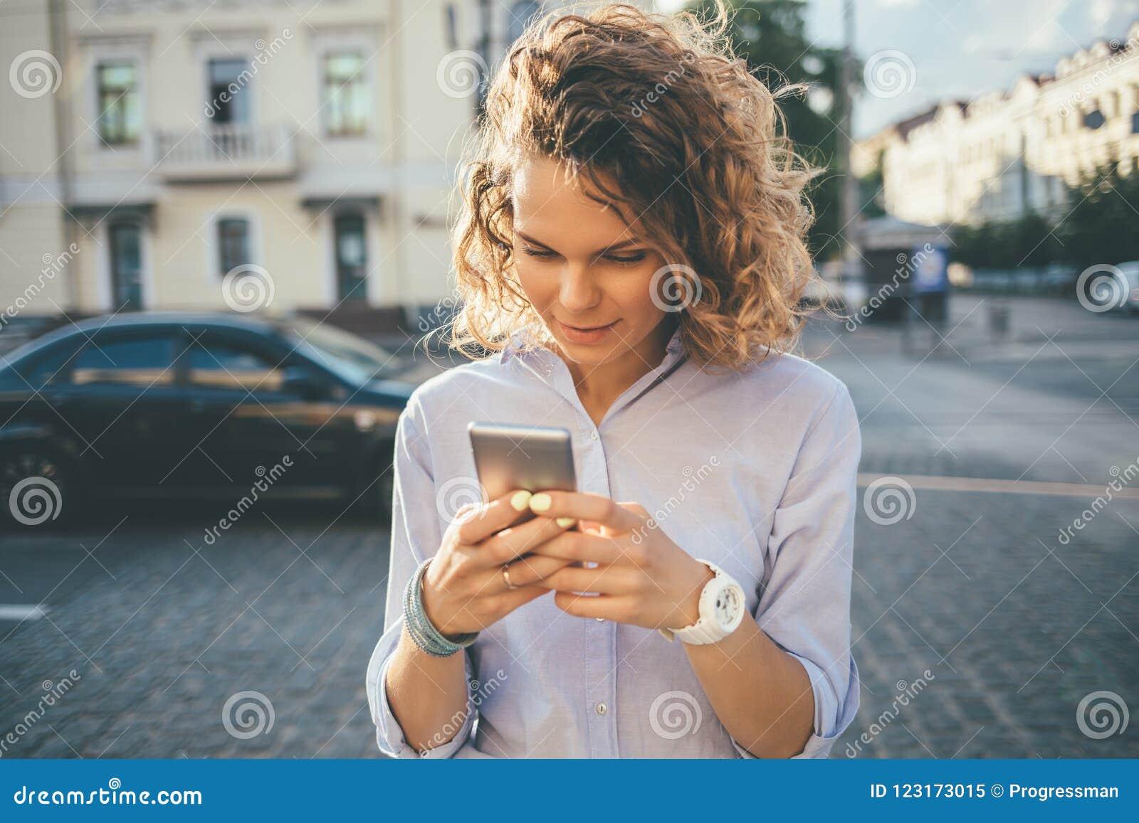 Giovane donna felice che porta camicia blu facendo uso del telefono cellulare