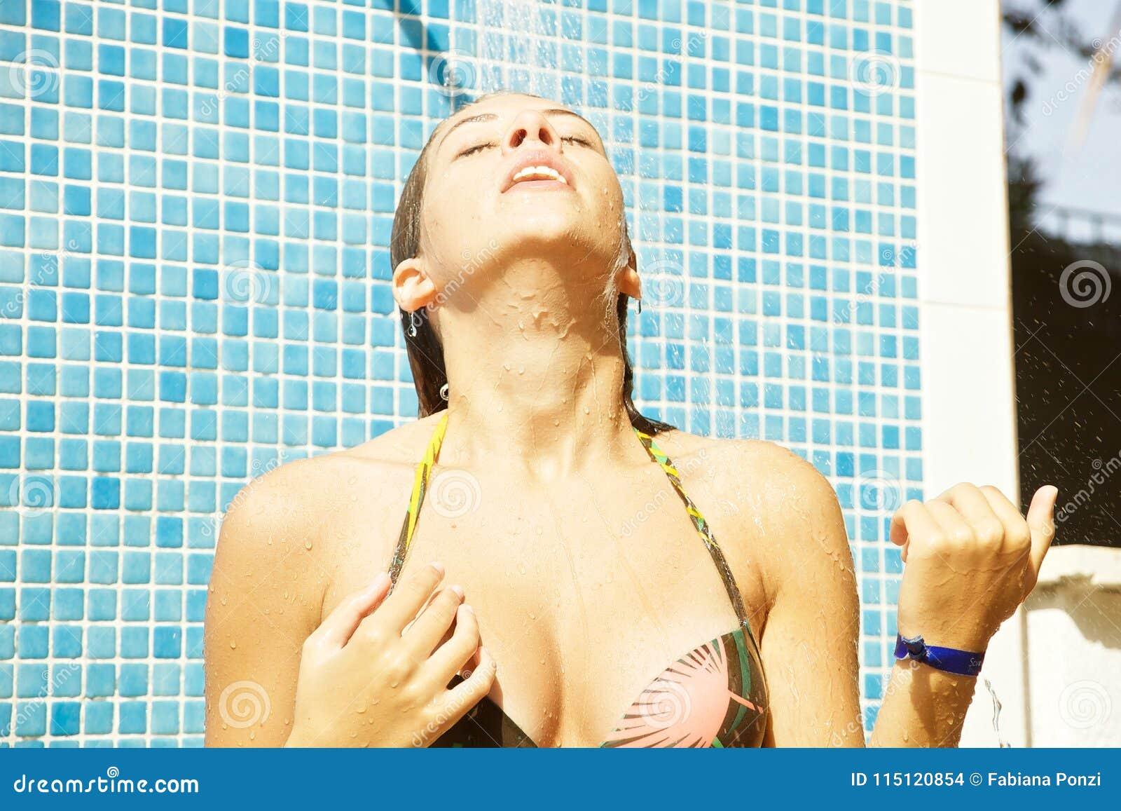 Giovane donna felice che prende doccia nel rilassamento esteriore