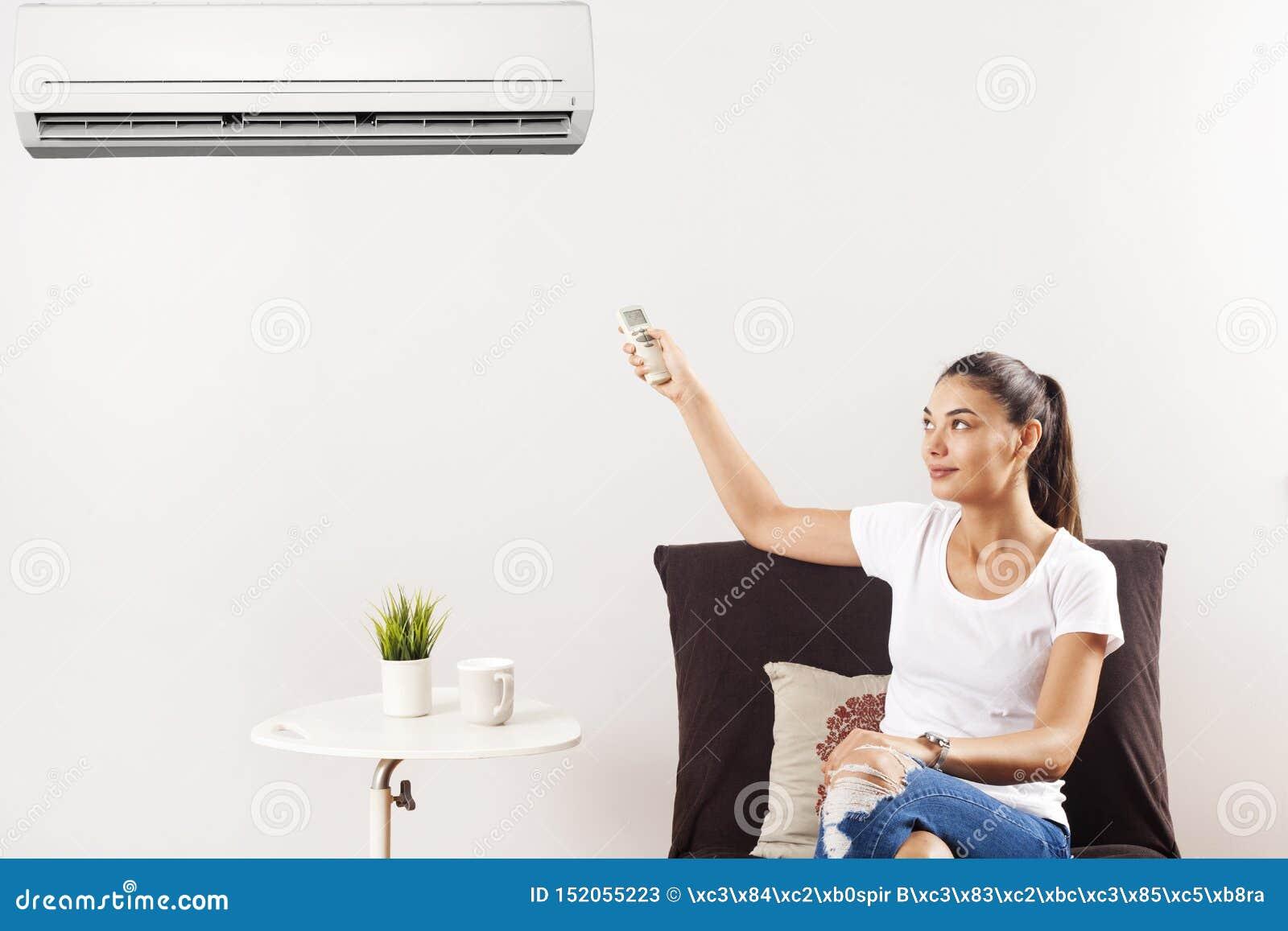 Giovane donna felice che si siede sul condizionatore d aria di funzionamento dello strato con telecomando a casa