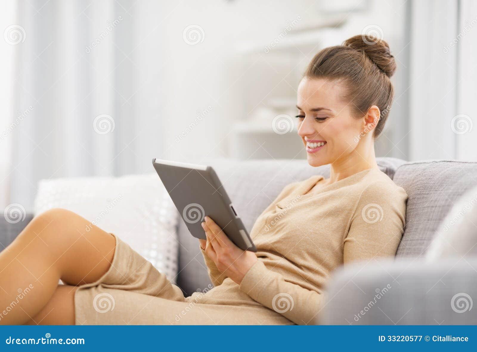 Giovane donna felice che si siede sullo strato e che lavora al pc della compressa