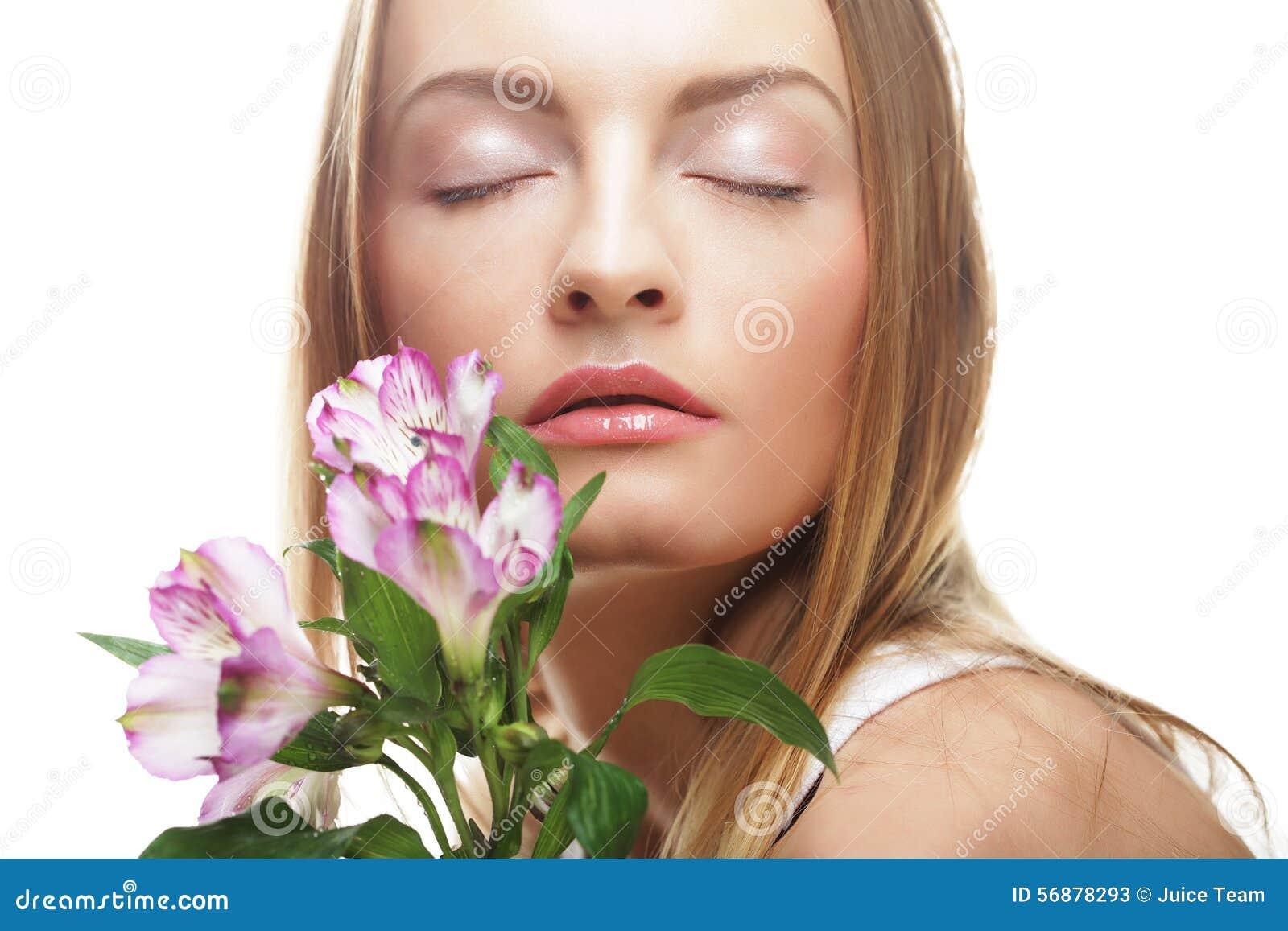 Giovane donna felice con i fiori rosa
