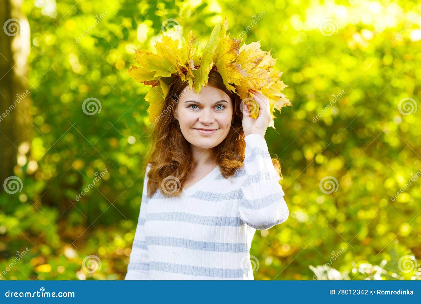 Giovane donna felice con la ghirlanda delle foglie di acero di autunno in parco