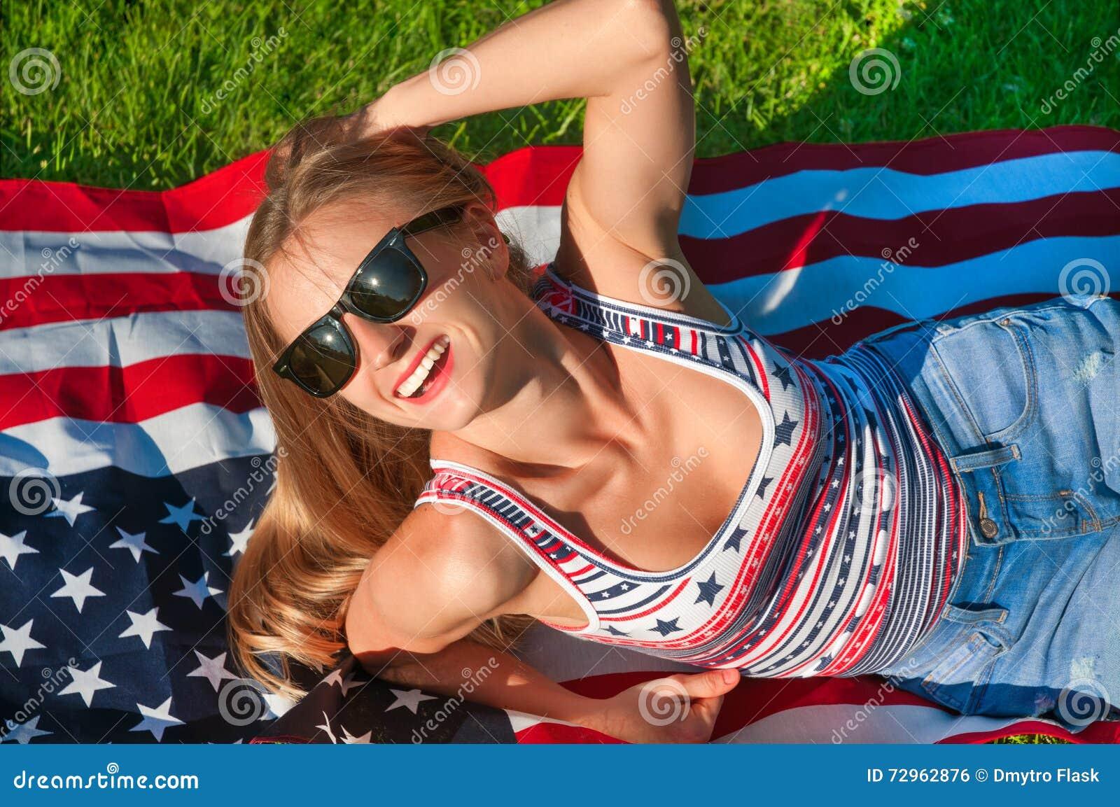 Giovane donna felice del patriota sulla bandiera degli Stati Uniti