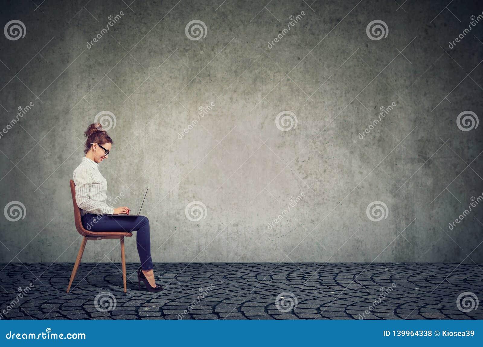 Giovane donna felice di affari che si siede su una sedia facendo uso del suo computer portatile