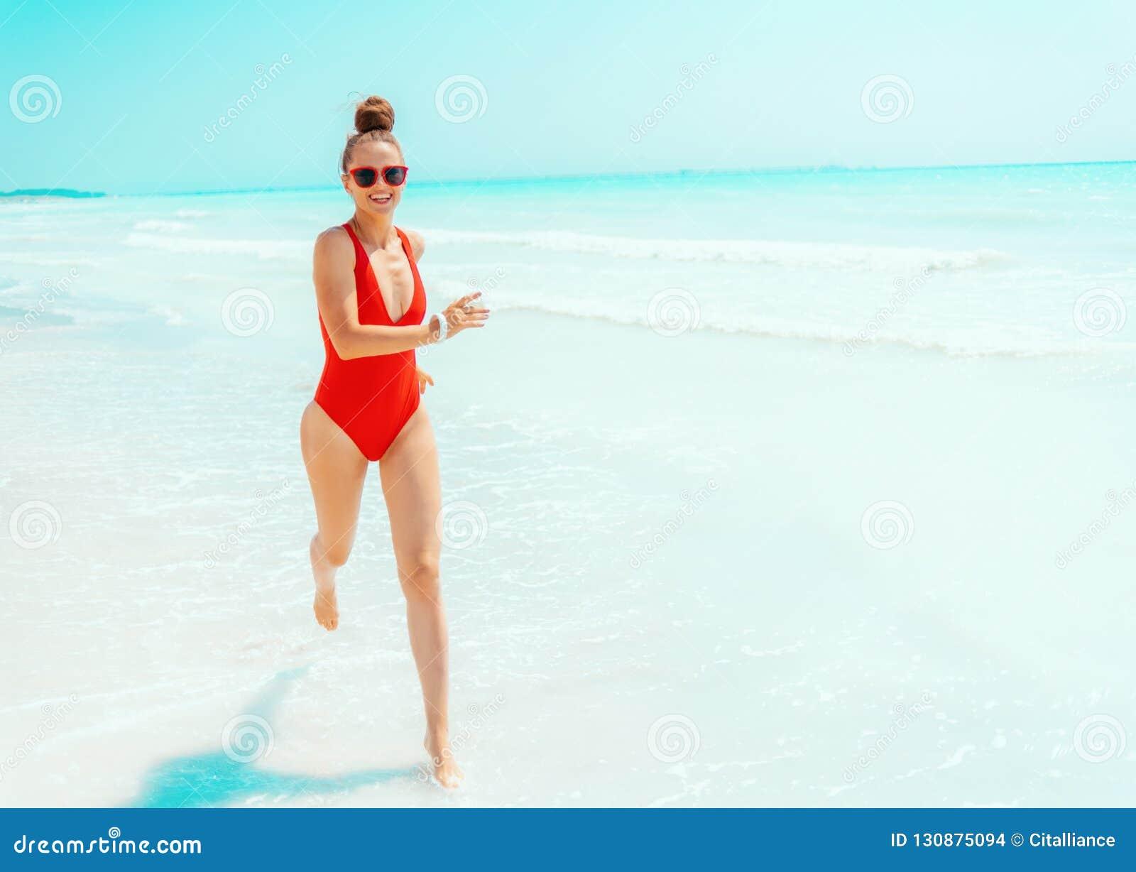 Giovane donna felice in swimwear rosso su funzionamento della spiaggia