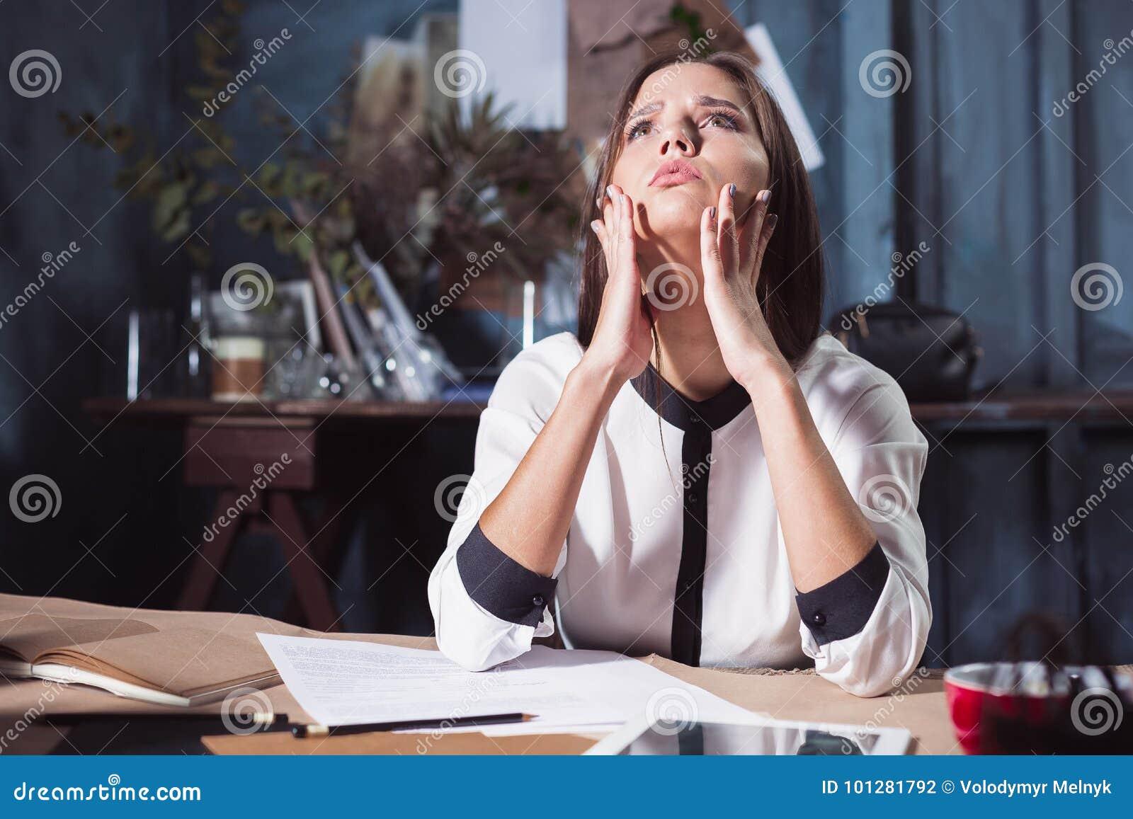 Giovane donna frustrata che lavora alla scrivania davanti al computer portatile