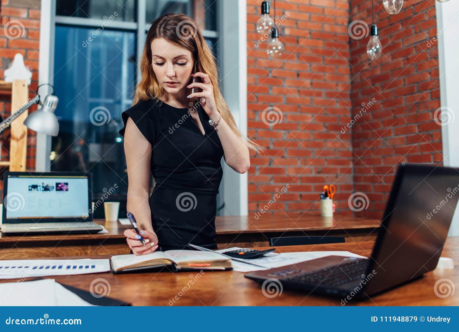 Giovane donna graziosa che parla sul telefono che conta facendo uso di un calcolatore che funziona all ufficio che sta allo scrit
